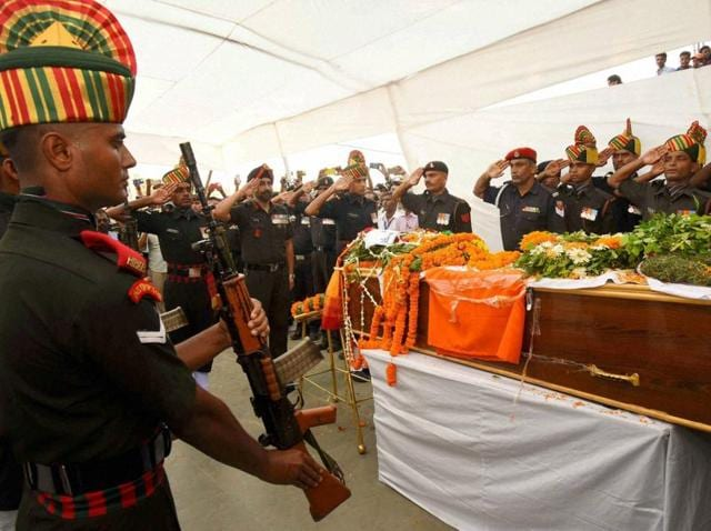 A police officer pays tribute to Sunil Kumar Vidyarthi who was killed in Uri, during his funeral in Gaya on Tuesday.
