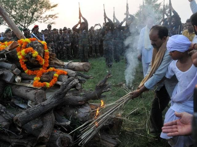 Son lights the pyre of Havildar Ravi Paul of 10 Dogra Regiment as soldiers fire in the air at his village Sarwah in Samba district, about 35 km from Jammu, on Monday. Paul and Subedar Karnail Singh from Jammu died in Sunday's militant attack in Uri.
