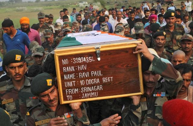 Relatives and villagers watch the funeral of Indian army soldier Gangadhar Dalai, who was killed in a militant attack in Uri, Kashmir, in Jamuna Balia village, west of Kolkata.