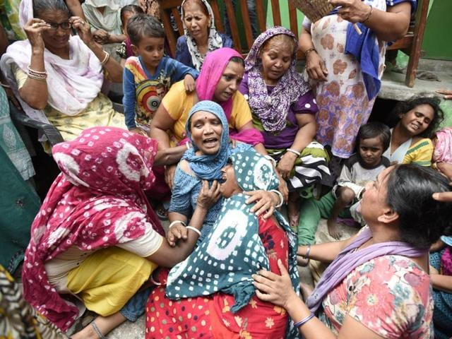 Family members mourn the death of their relatives in Nand Nagri on Tuesday.