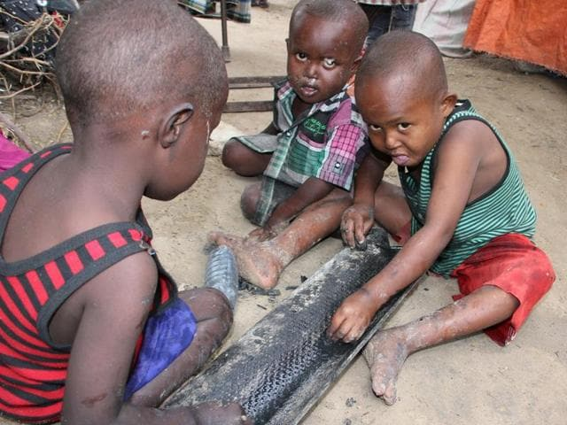 Children play on the ground outside their makeshift home in a refugee camp in Mogadishu, Somalia, A UNreport says more than 3,00,000 children under five are acutely malnourished.