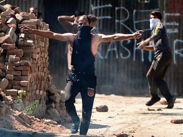 A Kashmiri holds bricks to throw at security personnel , September 13