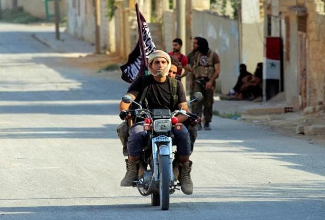Rebel fighters from the hardline jihadist Jund al-Aqsa ride on a motorbike in Taybat al Imam town after they advanced in the town in Hama province of Syria on August 31, 2016.