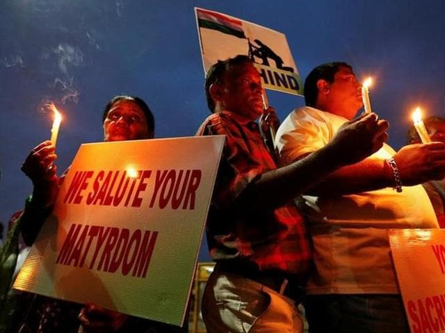 People hold candles and placards during a vigil for the soldiers who were killed after gunmen attacked an Indian Army base in Kashmir's Uri on Sunday, in Mumbai.
