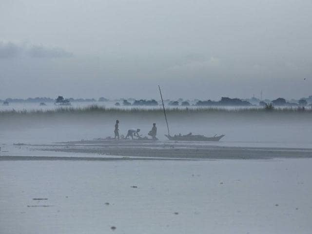 Villagers salvage logs of wood brought by flood waters of river Brahmaputra in Majuli, east of Gauhati in Assam  in July.