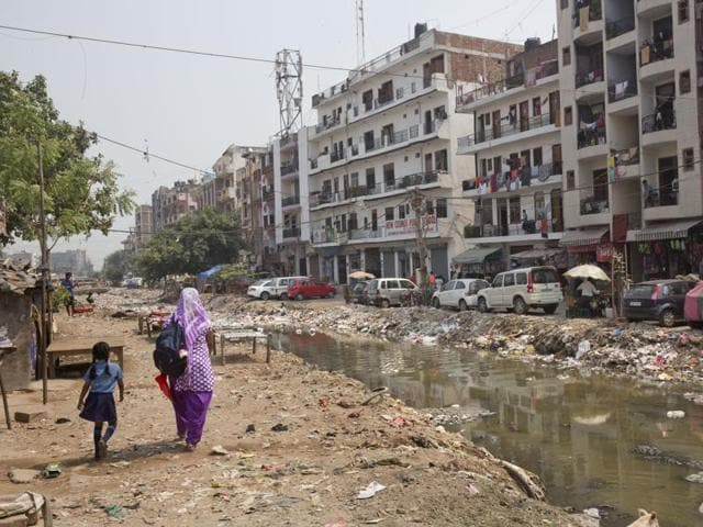 A woman walks with a child along an open drain filled with plastic and stagnant water, which act as a breeding ground for mosquitoes, in New Delhi.