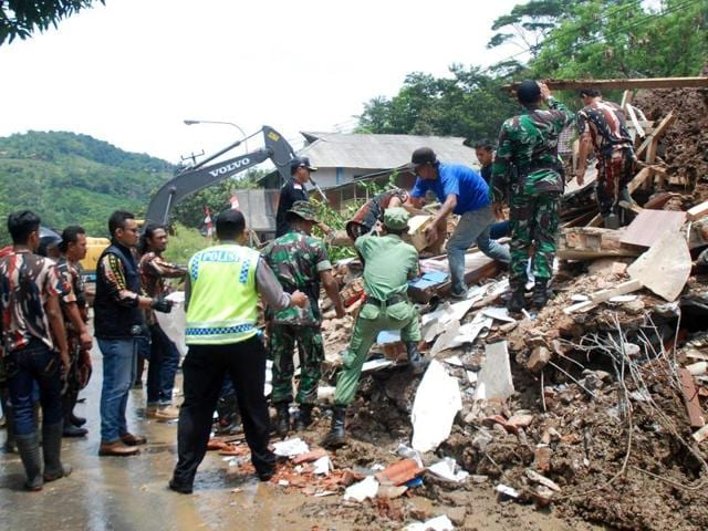 An Indonesian search and rescue team joined by volunteers remove debris from an area hit by a landslide in Sumedang.