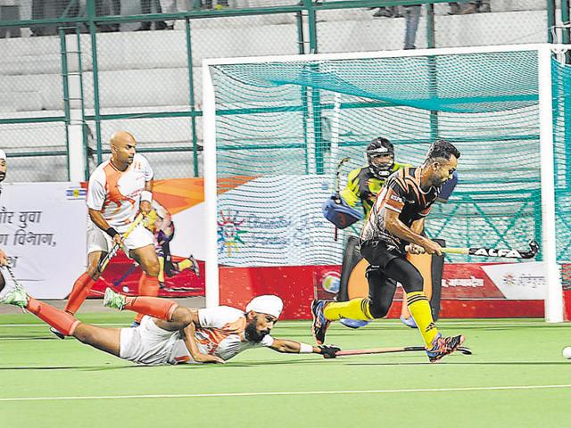 An Air India team defender trying hard to stop railway forward Affan Yusuf during semi-final match between Air India and Indian Railways in Obaidullah Khan heritage hockey cup at Aishbagh stadium in Bhopal, India, on Tuesday, September 20, 2016.