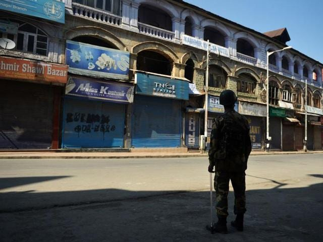 An Indian paramilitary trooper stands guard during a curfew in the Lal Chowk area of central Srinagar in Kashmir.