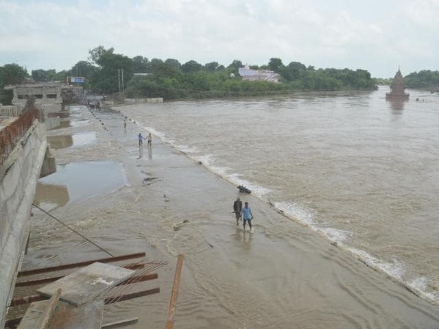 villagers carrying their belongings crossing Betwa river in Vidisha.(HT Photo)