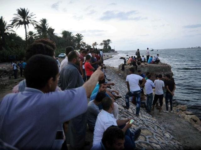 People gather along the shore of the Mediterranean Sea during a search for victims after a migrant boat capsized in Al-Beheira of Egypt on Wednesday.