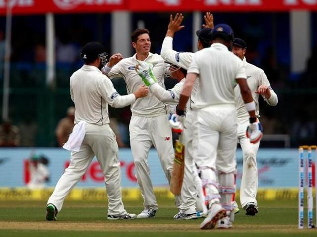 New Zealand's Mitchell Santner (C) celebrates the wicket of India's Lokesh Rahul.