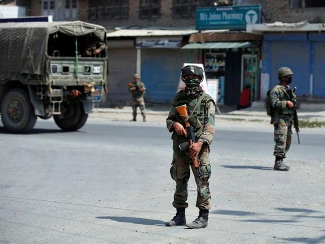 Indian army soldiers stand guard on a street on the outskirts of Srinagar.