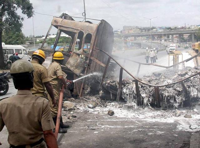 Fire men douse a torched truck in Bengaluru after violent pro-Kannada activists rampaged through the city over the Cauvery water row.