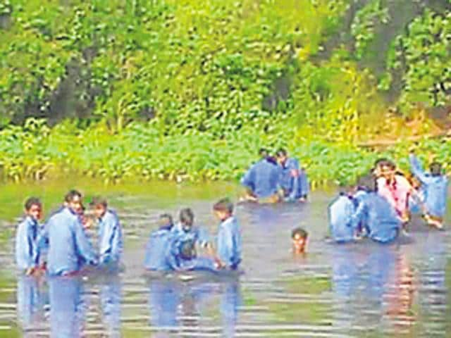 Children from three villages use inflated rubber tubes to cross the Bhainsavat to reach their school.