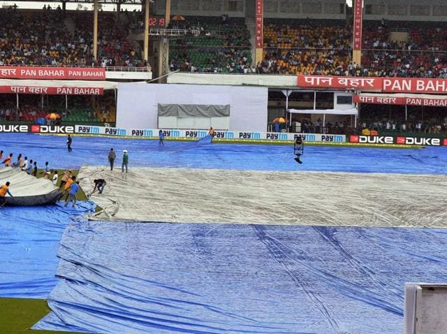 Kanpur: Groundsmen cover the pitch as it rains during the first Test match between India and New Zealand at Green Park in Kanpur on Friday. PTI Photo by Atul Yadav (PTI9_23_2016_000083A)