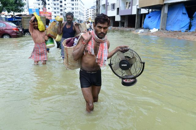 Residents carry their belongings along a flooded street, following heavy rain in Nijampet, a low lying area on the outskirts of Hyderabad on September 21, 2016.