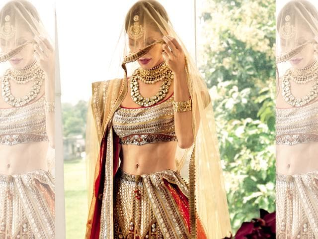 """Veiled  surprise: Embroidery done by hand, laser cut gota, gold and silver thread, mirrors, and acrylic antiquate give this JJ Valaya's perfect bride of 2016 a vintage look. Says stylist Eshaa Amin, """"A red lehenga with a tube choli has a safe bridal vibe. If you are not confident or well-toned enough to flash that midriff, try a longer choli."""" (Jadau jewellery from Amaris-jewels by Prerna Rajpal's Mughal heritage collection)"""