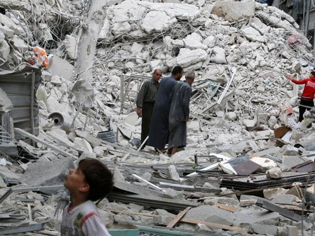 People inspect a damaged site after airstrikes on the rebel held Tariq al-Bab neighbourhood of Aleppo, Syria.