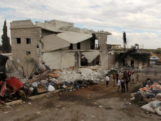 People stand near damaged aid supplies after an airstrike on Tuesday on the rebel held Urem al-Kubra  town.
