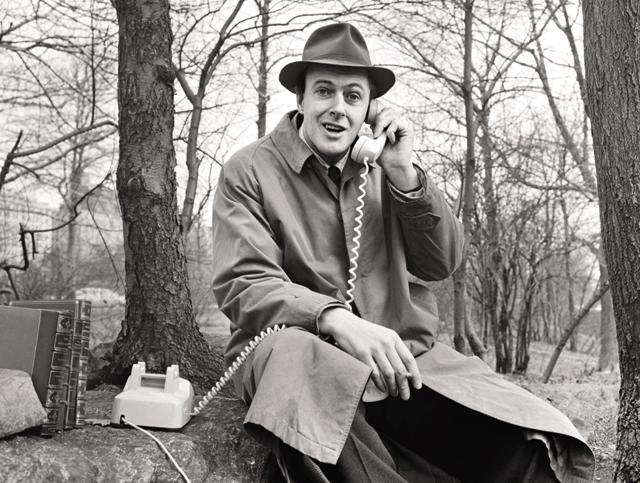 Roald Dahl answers a telephone while filming an episode of the science fiction show
