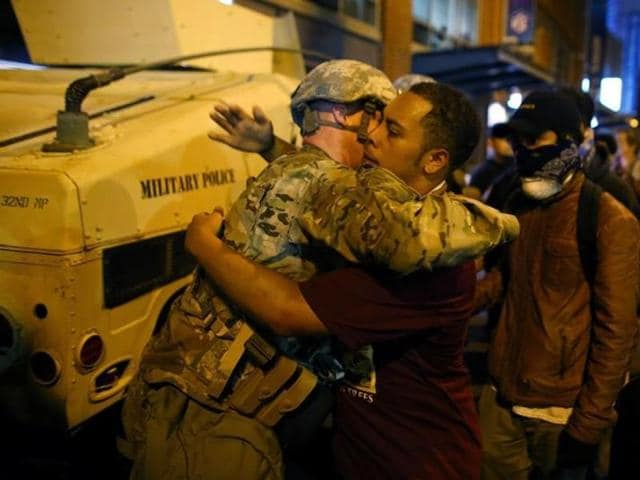 A US National guard soldier accepts a hug from protester as people march through downtown to protest the police shooting of Keith Scott in Charlotte, North Carolina.