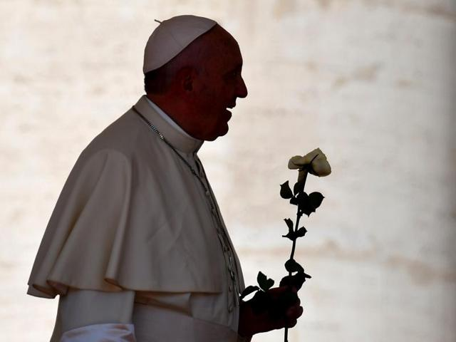 Pope Francis holds a rose in St Peter's square at the Vatican on September 3, 2016 upon his arrival for a catechism with nuns of the Missionary of Charity, the Religious family founded by Mother Teresa.