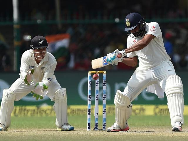 India's Rohit Sharma, center, raises bats after scoring fifty runs on the fourth day.(AP Photo)