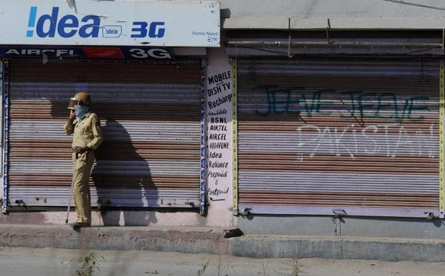 A policeman speaks on a mobile phone in front of closed shops during clashes in Srinagar.