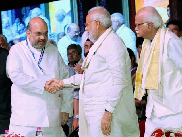 Prime Minister Narendra Modi shakes hands with BJP president Amit Shah during BJP's National Council Meeting at Kozhikode on Sunday.(PTI)