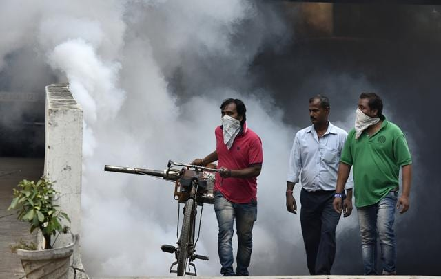 Municipal workers fumigate the parking lot at Mandi House in New Delhi on Monday.