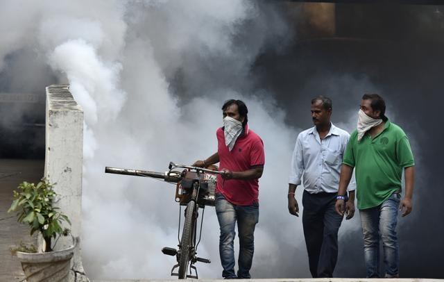 Municipal workers fumigate the parking lot at Mandi House in New Delhi on Monday.(Raj K Raj/HT Photo)