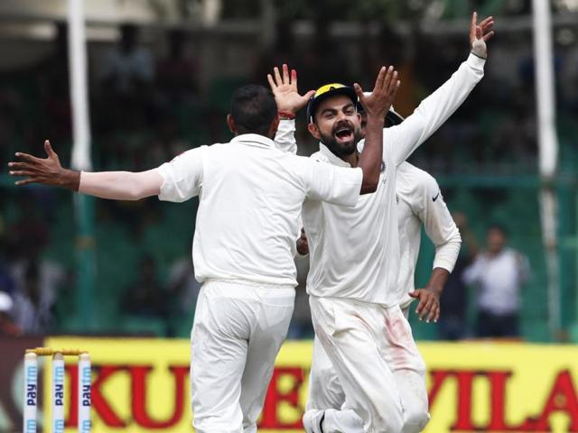 India's captain Virat Kohli celebrates the wicket of New Zealand's BJ Watling with bowler Mohamed Shami (left) on the fifth day of their first cricket Test match at Green Park Stadium in Kanpur.