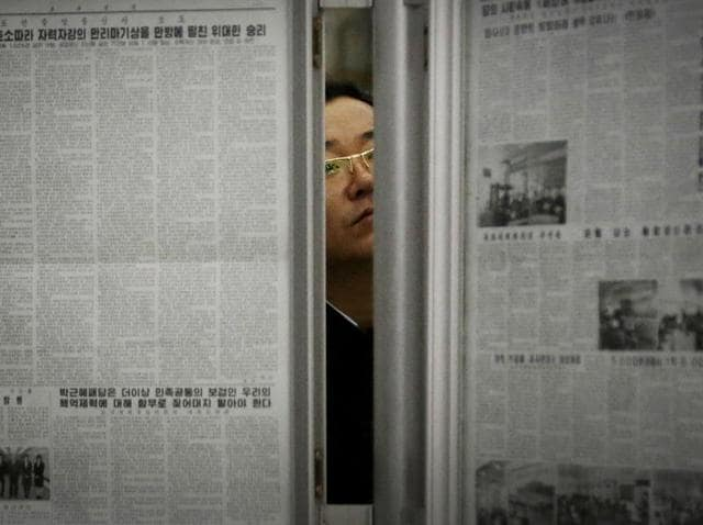 A North Korean man reads the local newspapers displayed in a subway station as seen during a press tour in Pyongyang, North Korea.
