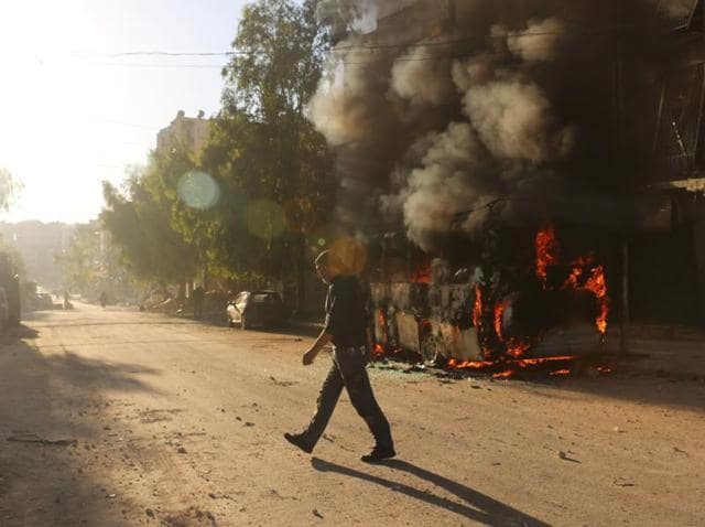 A Syrian man walks past a bus set ablaze following a reported air strike in the rebel-held Salaheddin district of Aleppo.