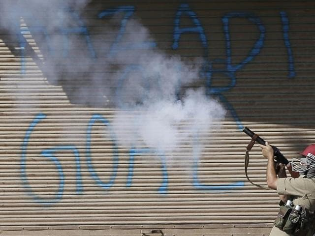 A policeman fires a tear gas shell on Kashmiri protesters in front of a graffiti on shutters that reads