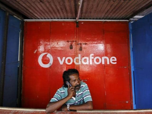 People walk past as a Vodafone logo is reflected in a side-view mirror of a bike outside its outlet in New Delhi.