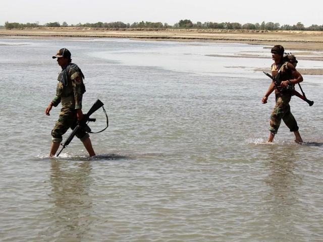 Afghan security forces patrol near the Alchin Afghan-Tajik transit bridge damaged by militants during fighting in Kunduz.