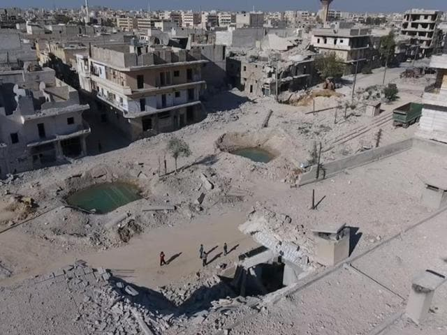 A still image taken on September 27, 2016 from a drone footage obtained by Reuters shows people standing near craters and damaged buildings in a rebel-held area of Aleppo.