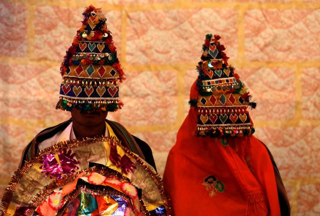 A bride and groom wearing traditional handmade garlands wait for their wedding to start during a mass marriage ceremony in the southern Pakistani city of Karachi.