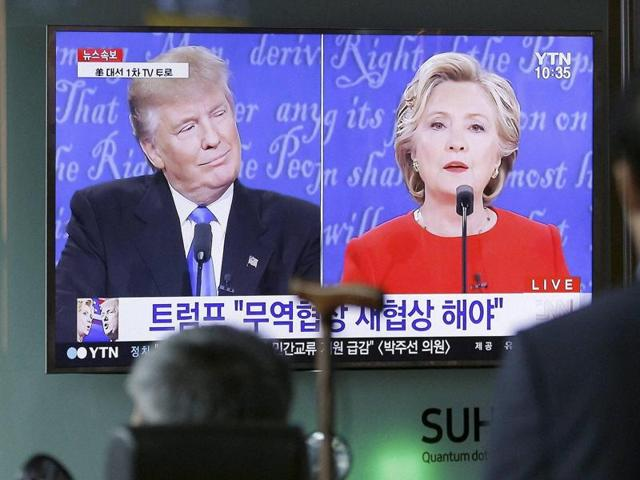 People in Seoul watch a TV screen showing the live broadcast of the US presidential debate between Democratic presidential nominee Hillary Clinton and Republican presidential nominee Donald Trump.