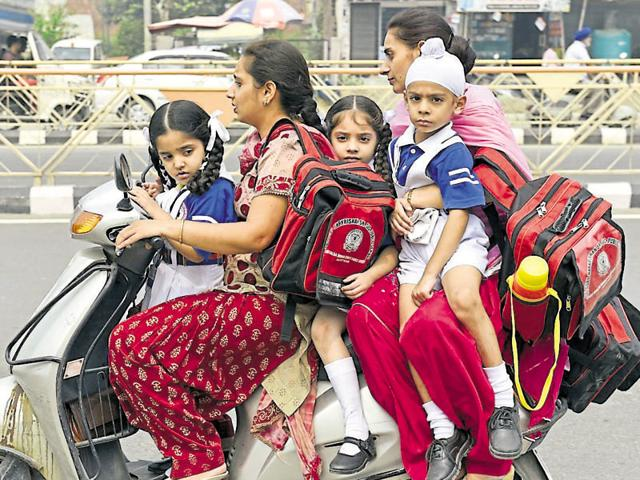 Parents picking up their children from school during the strike of school van operators in Amritsar on Monday.