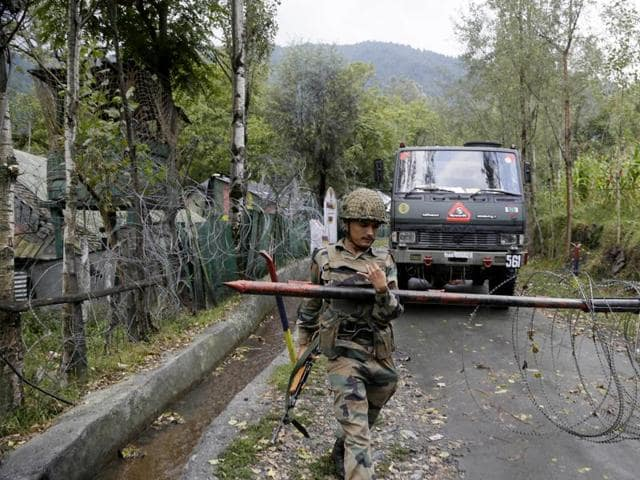 An Indian army soldier lifts an iron barricade to allow a vehicle to drive out of a military base at Braripora in Kashmir.