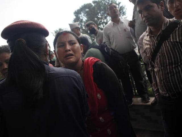 Family members of injured passengers, rescued after an overcrowded bus slipped off a mountain road gather at the Teaching hospital in Kathmandu, Nepal.