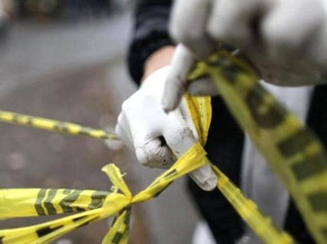 A forensic technician ties a used police line together to seal off a crime scene.