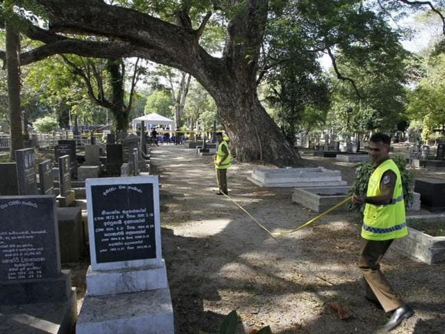Sri Lankan crime investigating police officers prepare to exhume the remains of murdered newspaper editor Lasantha Wickrematunge at a cemetery in Colombo on Tuesday following a court order for a fresh investigation. Wickrematunge, editor of the Sunday Leader newspaper, was killed while driving to work in January 2009.