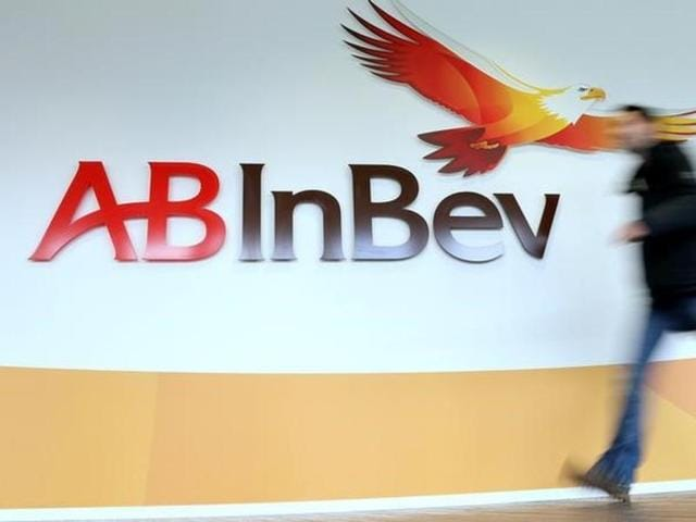 A man walks past the logo of Anheuser-Busch InBev at the brewer's headquarters in Leuven, Belgium.