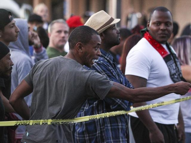 A man points at police as he and others yell while at the scene where a black man was shot by police in El Cajon, east of San Diego, California.