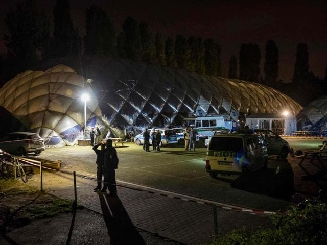 Policemen stand in front of an airdome housing a refugee shelter in Berlin, where a 29-year-old refugee was shot dead by the police.