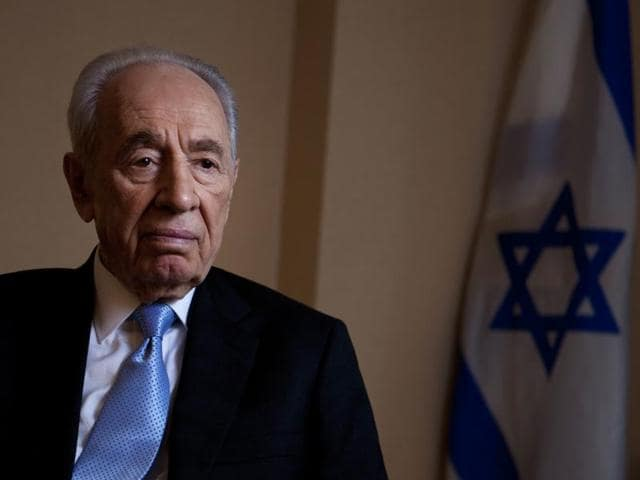 A woman shows her support as she holds up a photograph of herself with former Israeli President Shimon Peres during a briefing to members of the media on the medical condition of Peres a day after he suffered a stroke, at a hospital near Tel Aviv, Israel September 14, 2016. Peres passed away on Tuesday morning.